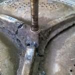 Estrella y eje, soporte de tambor, arruinada por el efecto cáustico del jabón líquido.